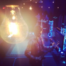 light bulb glowing over a musician playing a guitar on stage