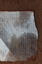 Writing on notebook paper in the dirt.