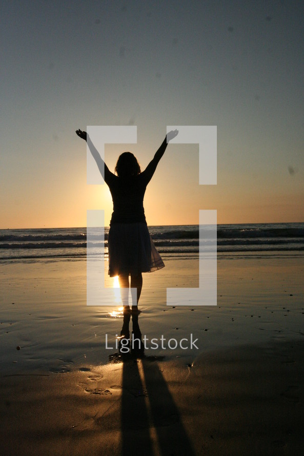Woman on beach with hands raised to the sky