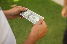 Hands holding paper money in yard.