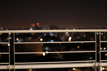 City lights in the background through a rail