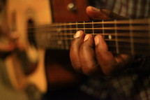 Man's fingers playing guitar