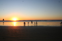 People playing jump rope on beach at sunset