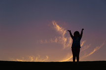silhouette of a girl child with raised hands at sunset