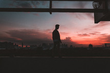 a silhouette of a man standing outdoors at sunset and a city view