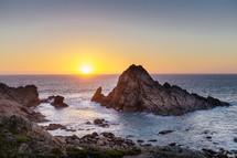 An ocean sunset and a rocky shore.
