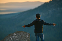 a man with outstretched arms standing on a mountaintop looking out at the view