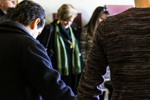 holding hands in prayer in a Bible study classroom