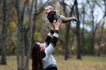 a mother tossing a baby in the air