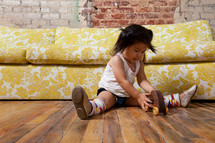 Asian toddler girl on the floor with a toy car