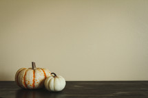 two pumpkins on a wood table