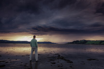 man standing on a shore at sunset