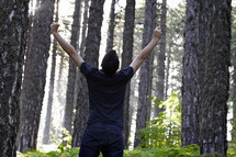 man with his hands raised in worship to God in a forest