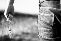 man holding a rosary at his side