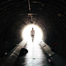 man walking in a tunnel
