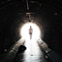 man walking in a tunnel