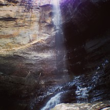 Sunlight beaming through limestone cavern with water running through it.