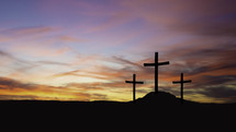 three crosses on a hill at sunset