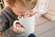 child holding a mug of hot cocoa with a candy cane