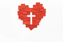 A heart made of red squares of paper with a white cross in the middle.