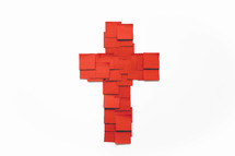 A cross made of red squares of paper on a white background.