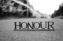 "Letters spelling ""honour"" on the pavement."