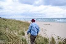 A man walks along an ocean beach with.
