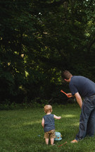 Father and son playing in backyard.