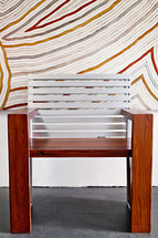 A modern wood chair against a painted striped wall