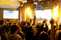 A group of people with hands raised worship service crowd