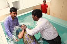 woman being dunked during a Baptism in India