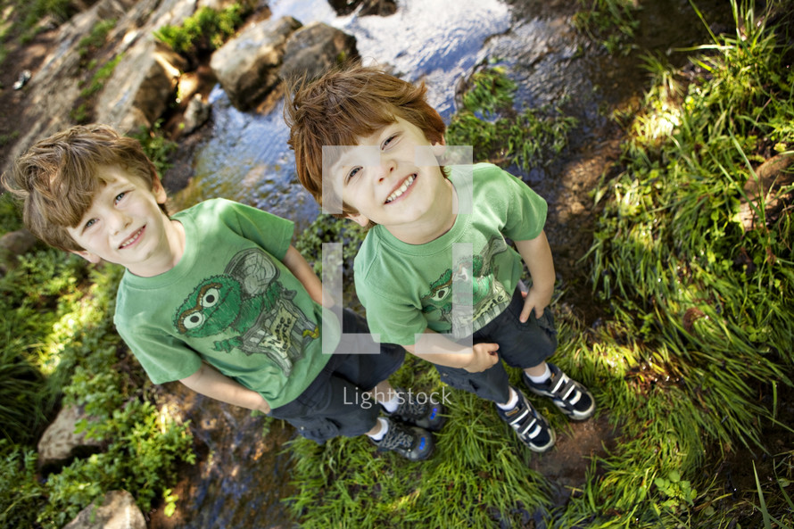 brothers standing in front of a stream