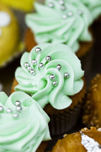 Chocolate cupcakes with green frosting and silver beads