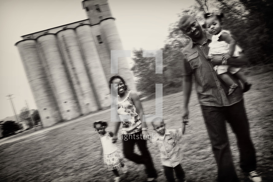 Family holding hands in front of a grain silo.