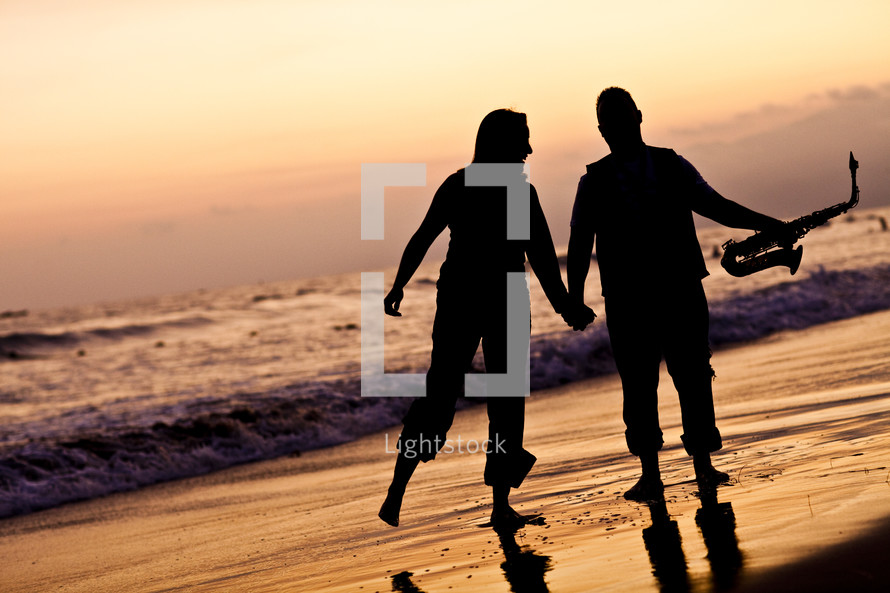 silhouette of a man and a woman holding hands on a beach holding a saxophone