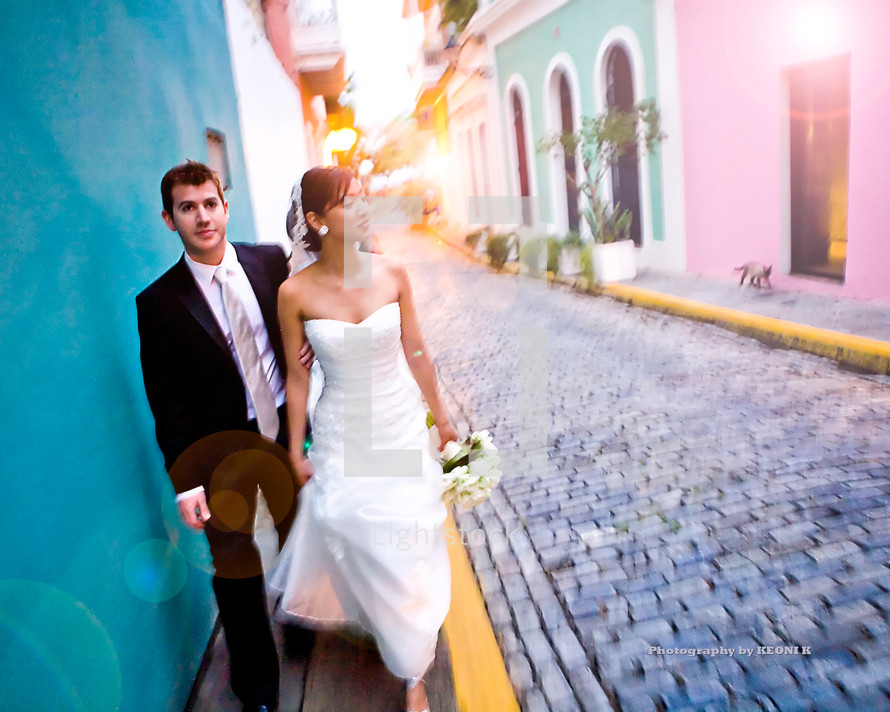bride and groom walking on a sidewalk next to a cobble stone street
