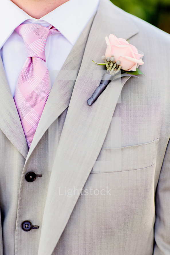 Mans grey suit with pink checker tie pink rose boutonnière