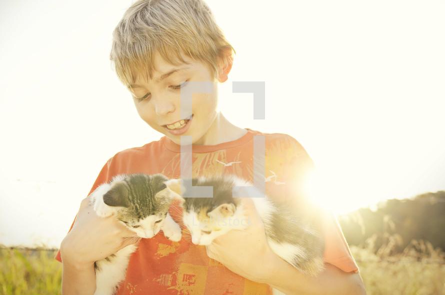 A boy holding kittens.