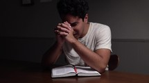 a man reading a Bible and praying