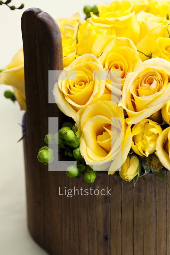 Flower arrangement yellow roses in wood vase basket