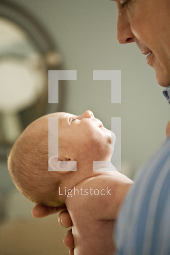 man holding and looking at a newborn