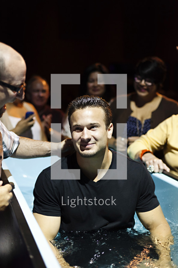 A smiling man being baptized content joy