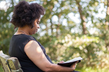 an African American woman sitting on a bench reading a Bible outdoors