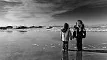 Children in jackets standing on water at the beach.