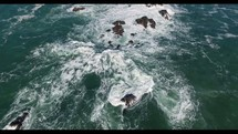 Aerial Video Bird's Eye Shot of Waves Crashing Against Rocky Coastline