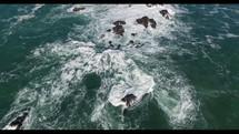 Aerial Video Bird's Eye Shot of Waves Crashing Against Rocky Coastline