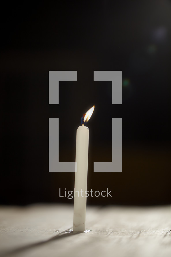 A single candle burns in the dark - lens flare