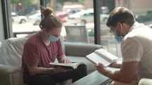 Men wearing face masks reading and discussing scripture in a coffee shop