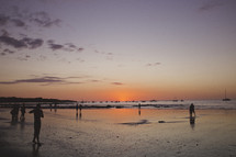 Silhouetted people on a beach at sunset