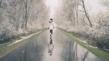 woman walking on a wet road in falling snow